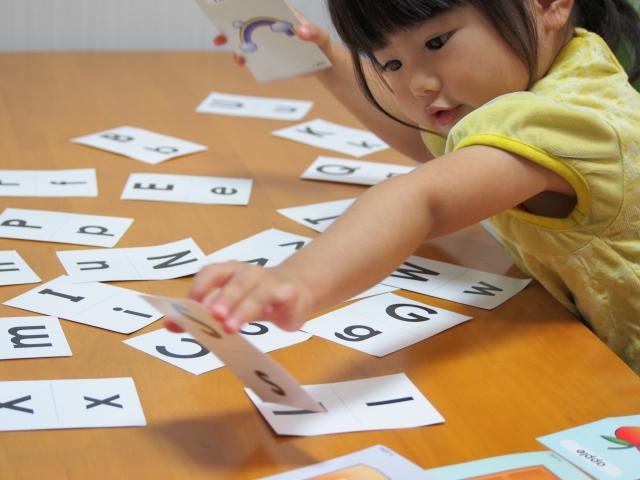 幼児が英語カードを取っている